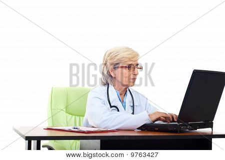 Senior Woman Doctor Typing On Laptop