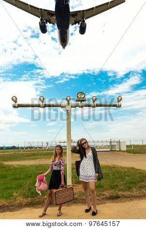 Two girls hitchhiking a plane