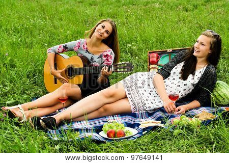 Two girls with guitar during picnic