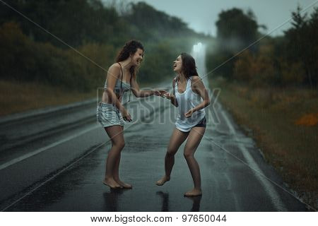 Girls Standing In The Rain On Roadway.