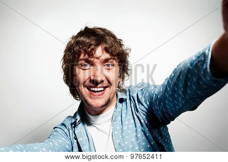 Close Up Portrait Of A Young Joyful Man Holding A Smartphone Digital Camera With His Hands And Takin