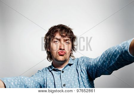 Close Up Portrait Of A Young Kissing Man Holding A Smartphone Digital Camera With His Hands And Taki