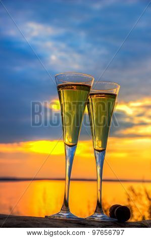 Two Glasses Of Champagne White Wine Standing On A Log