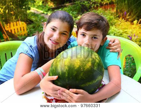 siblings with water melon on summer garden background