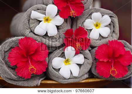 Towels with exotic flowers near the pool in a Balinese traditional spa