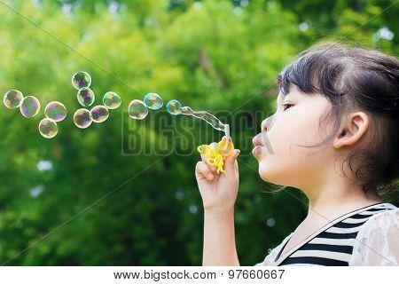 Asian Little Girl Blowing Soap Bubbles In Green Park