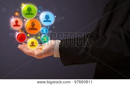 Businessman holding colorful social network icons in his hand