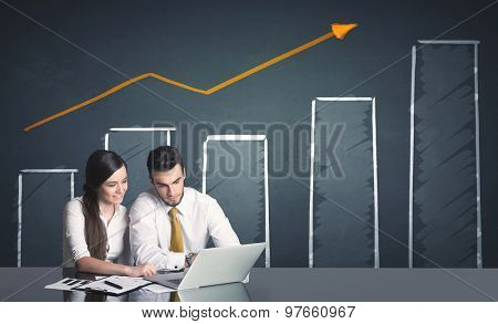Successful business couple with positive business diagram in background