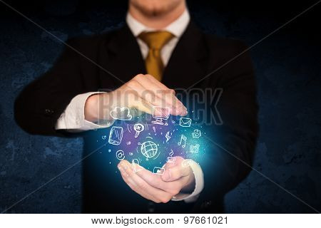 Businessman holding hand drawn media icons