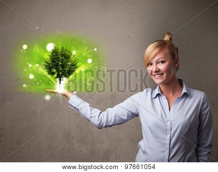 Young businesswoman holding a glowing tree in her hand