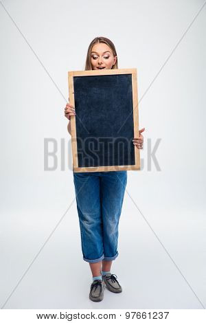 Full length portrait of a cute female student holding blank board isolated on a white background
