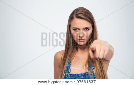 Young woman pointing finger at camera isolated on a white background