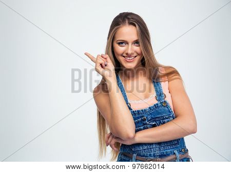 Portrait of a smiling young woman pointing finger away isolated on a white background. Looking at camera