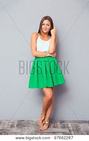 Full length portrait of a pretty girl posing on gray background