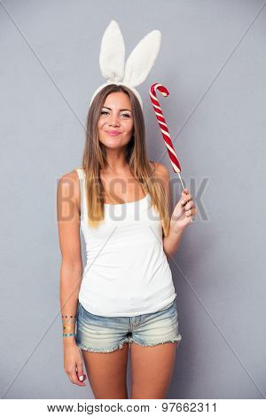 Pretty young girl with rabbit ears holding lollipop over gray background. Looking at camera