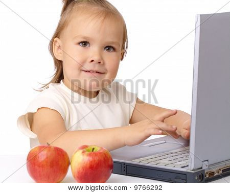 Cute Little Girl With Laptop And Two Apples
