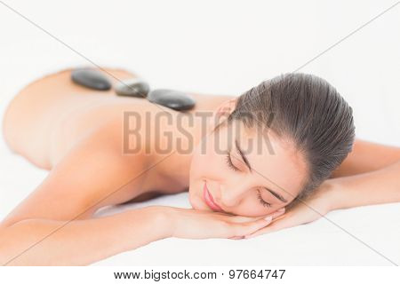 Pretty woman enjoying a hot stone massage at the health spa