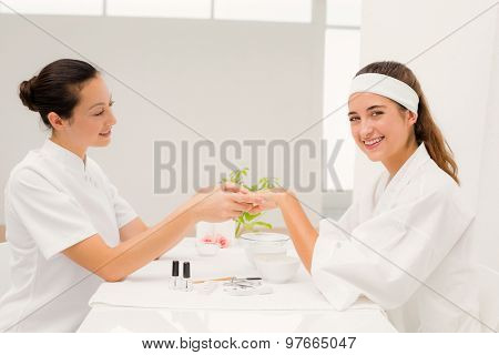 Close up of beautician applying nail varnish to female clients nails at spa beauty salon