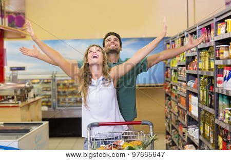 Happy bright couple buying food products at supermarket