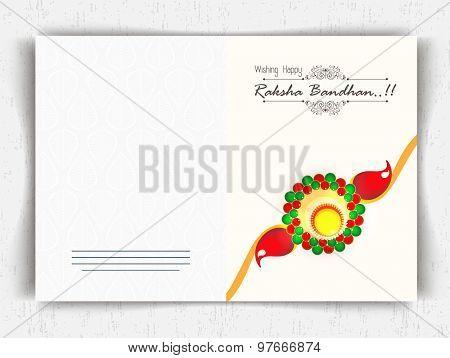 Creative greeting card design decorated with colorful rakhi on shiny background for Raksha Bandhan celebration.