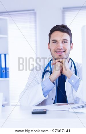 Portrait of smiling doctor looking at camera with hands folded in medical office