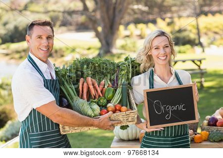 Farmer couple holding a vegetable basket and organic sign