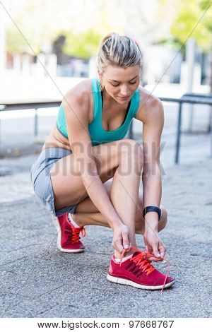 A beautiful woman tying her shoelaces on a sunny day