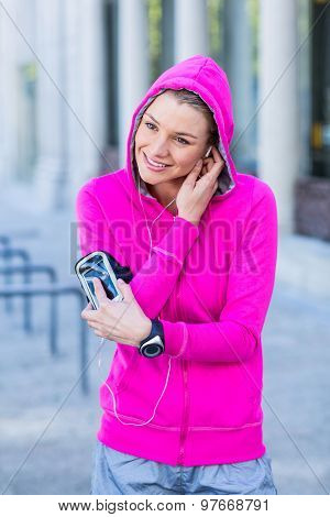 A woman wearing a pink jacket putting her headphones on a sunny day