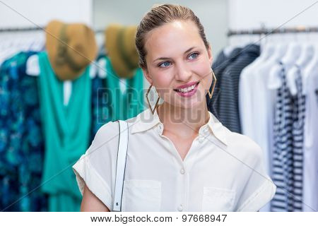 Smiling woman daydreaming in clothing store