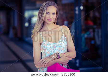 Portrait of smiling woman with shopping bag and arms crossed at shopping mall