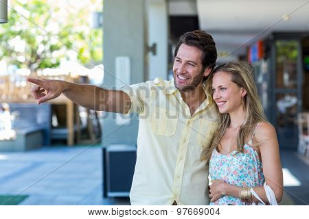 Smiling couple looking and pointing at shopping mall