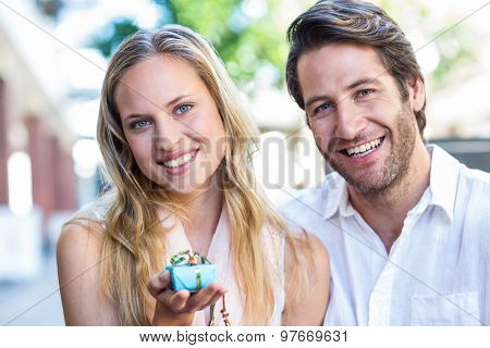 Portrait of smiling woman showing gift and sitting next to her boyfriend at shopping mall