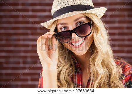 Portrait of gorgeous smiling blonde hipster posing with sunglasses against red brick background