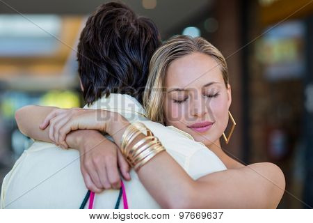 Smiling woman hugging her boyfriend with eyes closed at shopping mall