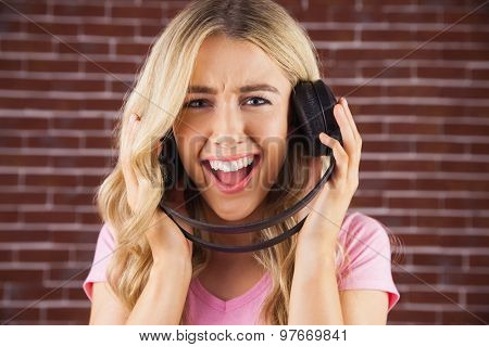Portrait of a beautiful woman with headphones singing against a red brick wall