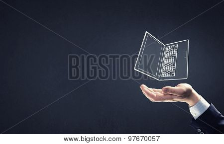 Human hand holding in palm laptop symbol