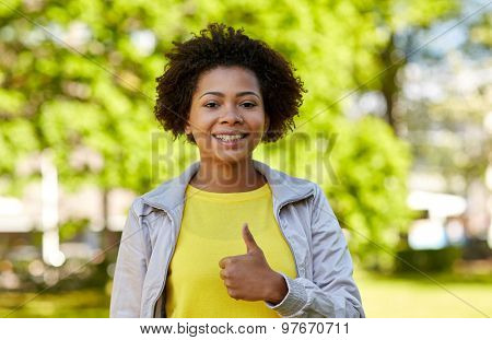 people, race, ethnicity and gesture concept - happy african american young woman showing thumbs up in summer park