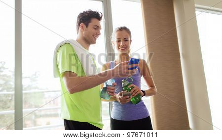 fitness, sport, technology and slimming concept - smiling young woman and personal trainer with smartphone and water bottles in gym