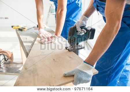 carpentry, building, teamwork and people concept - close up of builders with electric saw sawing board or wooden panel indoors