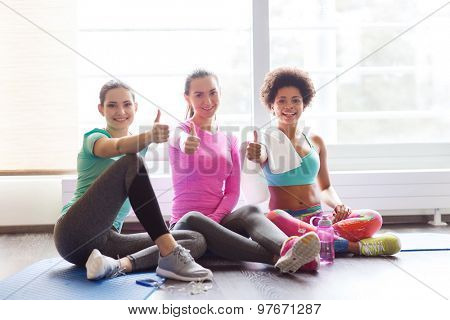 fitness, sport, training, gym and lifestyle concept - group of happy women with bottles of water showing thumbs up in gym