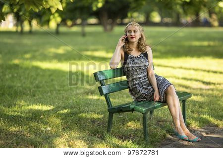 Young beautiful woman sitting on a Park bench talking on a cell phone.