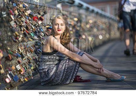 Young beautiful woman sitting on the bridge of love with padlocks.