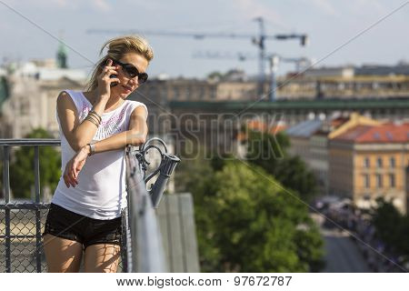 Pretty young blond woman talking on mobile phone outdoors in the city.