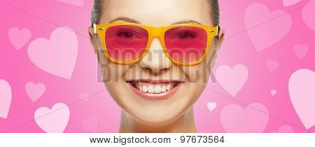 love, happiness, valentines day, face expressions and people concept - portrait of smiling teenage girl in pink sunglasses over background with hearts