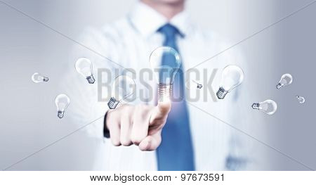 Close up of businessman touching with finger virtual light bulb