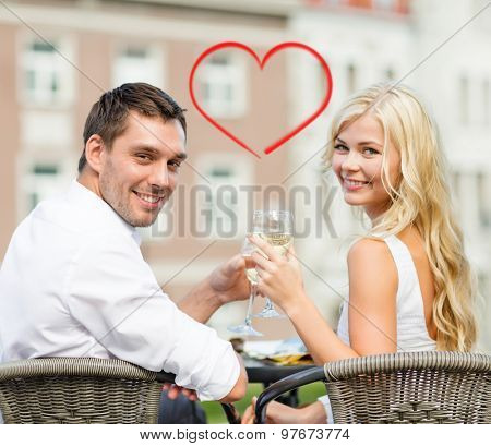 summer holidays and dating concept - smiling couple drinking wine in cafe in the city