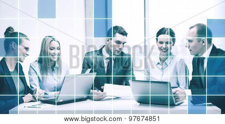 business, technology and people concept - smiling business team with laptop computers, documents and coffee having discussion in office over blue squared grid background