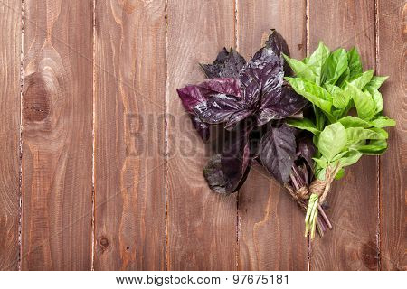 Fresh garden basil herbs on wooden table. Top view