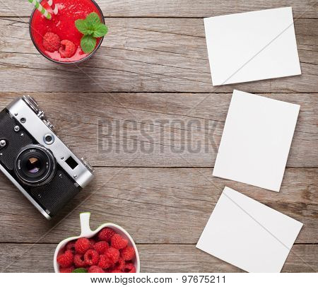 Vintage film camera, blank photo frames and raspberry smoothie on wooden table. Top view