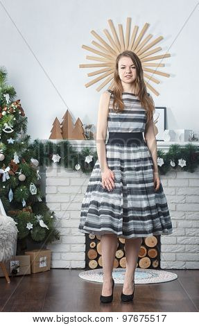 beautiful blonde girl standing around a Christmas tree
